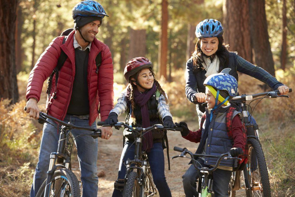 Glückliche Familie fährt mit ihren Fahrrädern durch den Wald, was passiert im Todesfall.