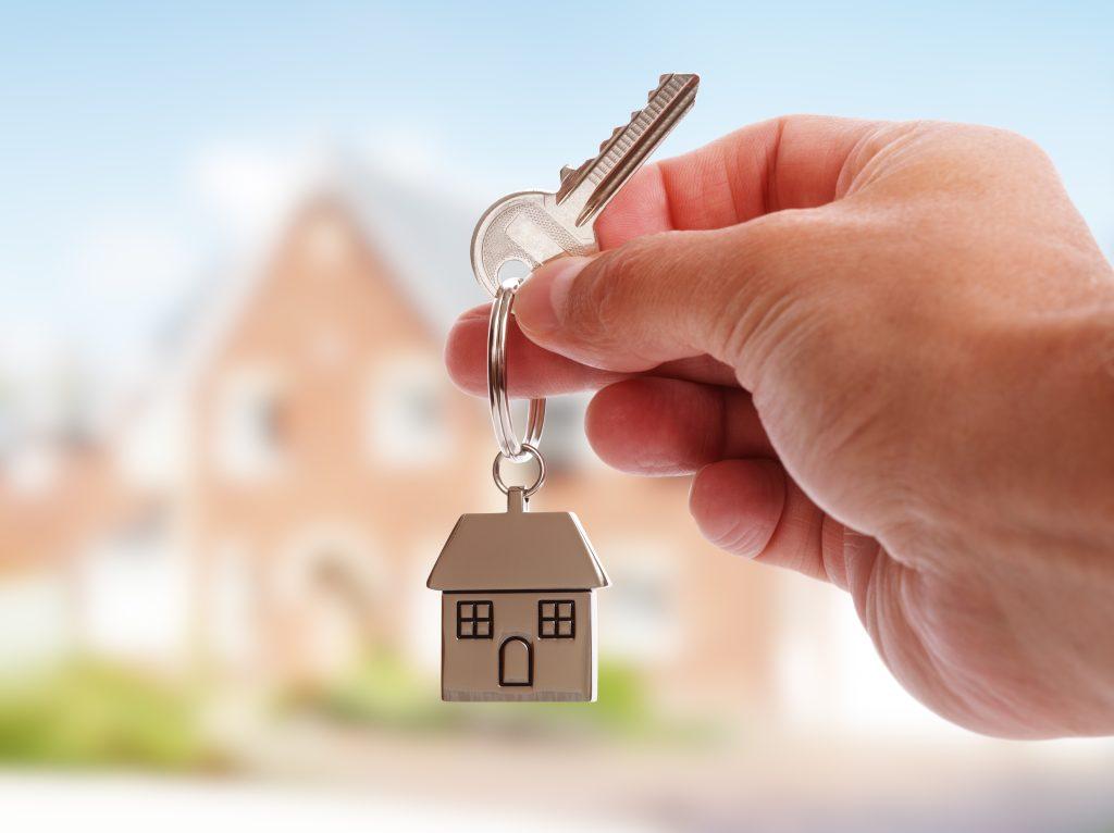 Nahaufnahme eines gehaltenen Hausschlüssels, welche die abgesicherte Baufinanzierung symbolisieren soll