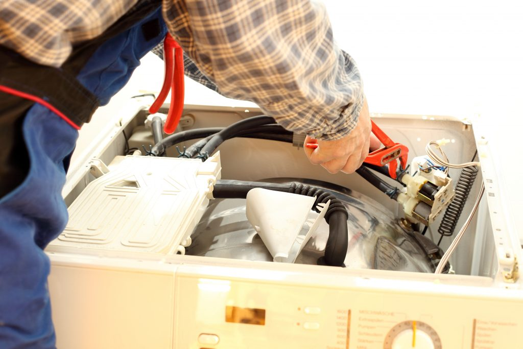 Klempner repariert ein Elektrogerät dessen Garantie abgelaufen ist