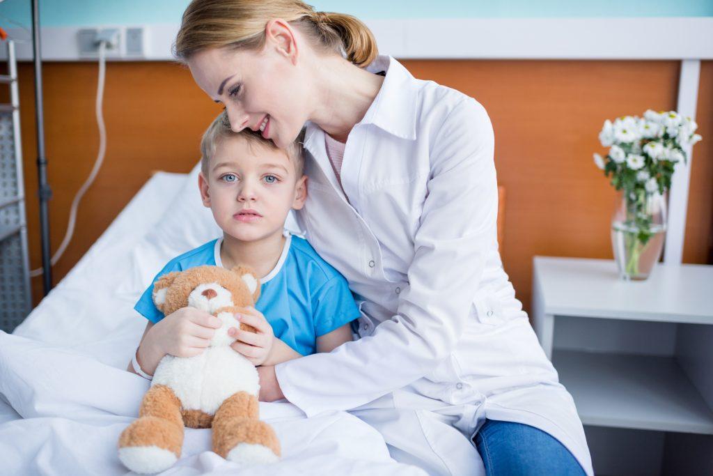 Mutter und Kind warten im Krankenhaus auf den Arzt währenddessen beruhigt die Mutter das Kind