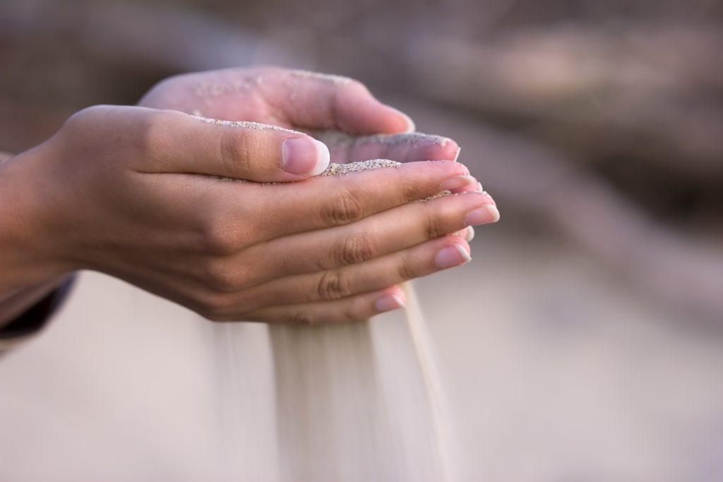 Sand fließt durch die Hände einer Frau, die sich die Frage stellt, was nach dem Tod bleibt
